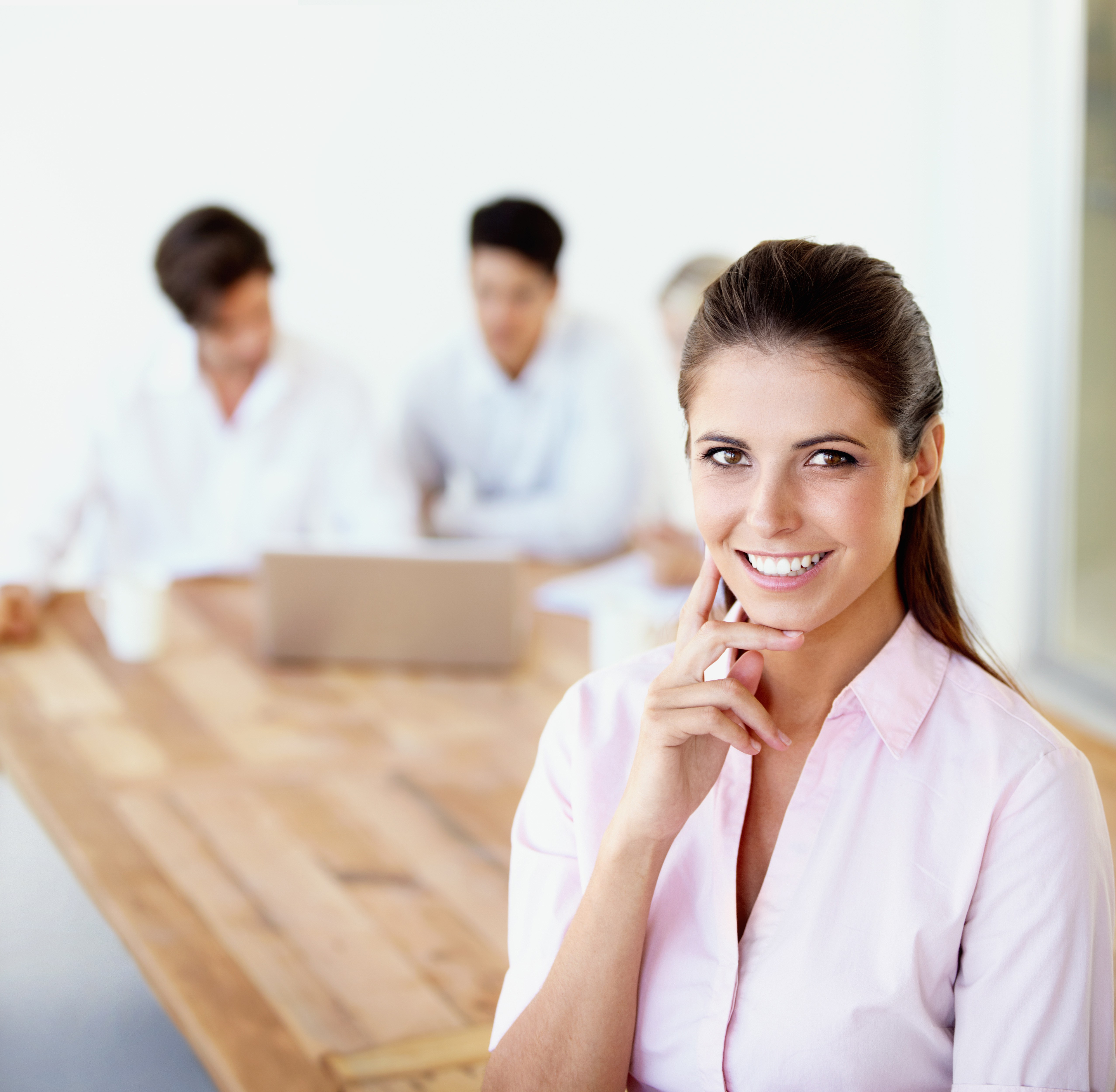 Smiling young businesswoman standing in the office with her team working in the background